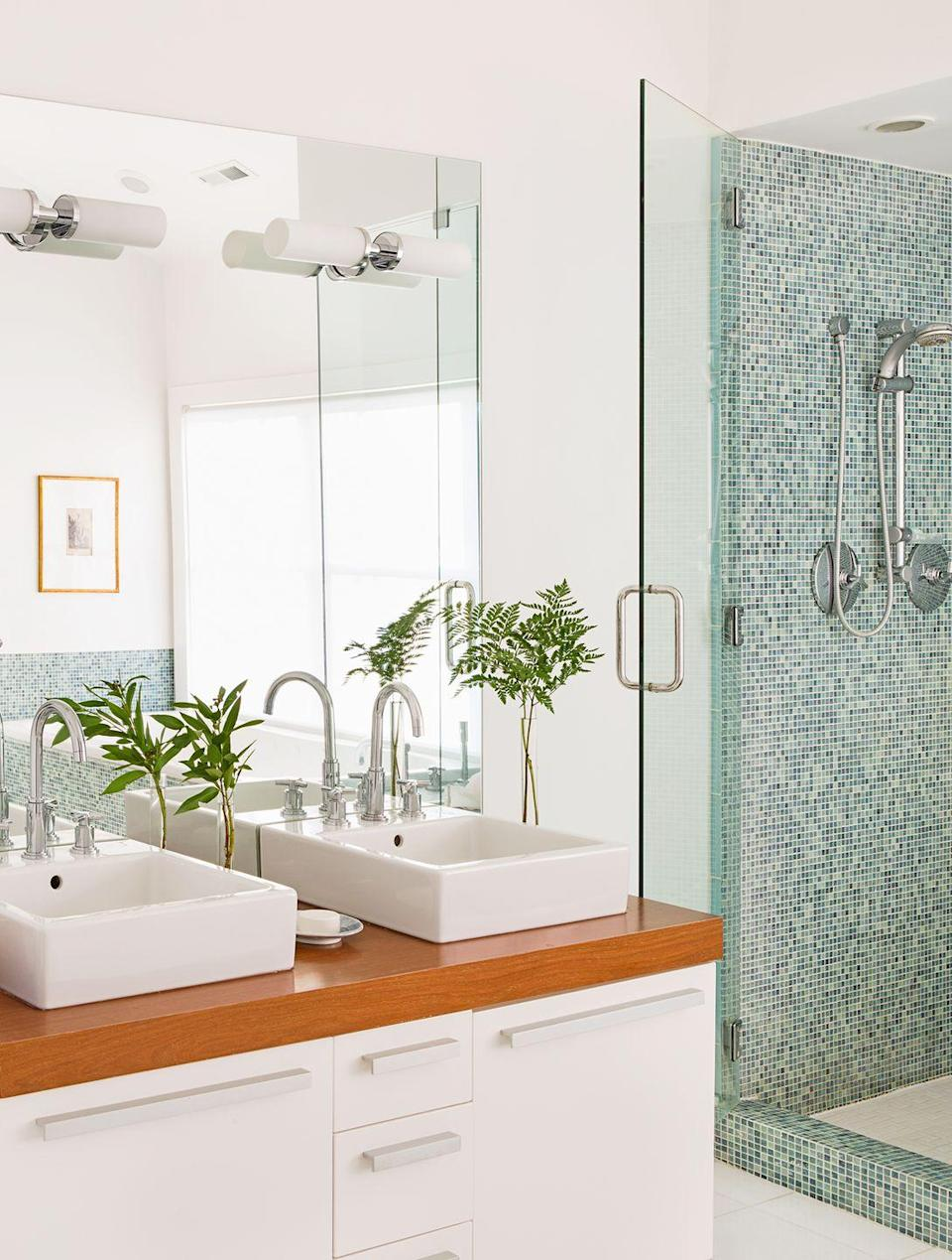 <p>Crisp white tones benefit from the shower stall's small watery blue tiles. </p>