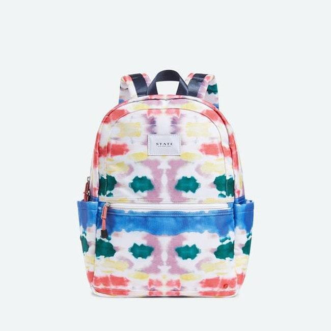 """Can't get enough of the tie-dye trend? Get this backpack with not one, but <em>two</em> <a href=""""https://www.teenvogue.com/story/best-reusable-water-bottles?mbid=synd_yahoo_rss"""" rel=""""nofollow noopener"""" target=""""_blank"""" data-ylk=""""slk:water bottle holders"""" class=""""link rapid-noclick-resp"""">water bottle holders</a>. $90, State. <a href=""""https://statebags.com/products/kane-kids-travel-printed-canvas-rainbow-tie-dye"""" rel=""""nofollow noopener"""" target=""""_blank"""" data-ylk=""""slk:Get it now!"""" class=""""link rapid-noclick-resp"""">Get it now!</a>"""