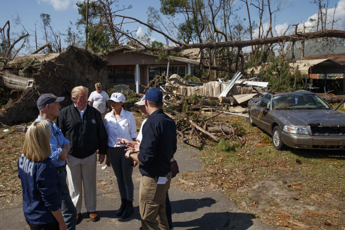 President Donald Trump talks with from left, Homeland Security Secretary Kirstjen Nielsen, Florida Gov. Rick Scott, Trump, first lady Melania Trump, Margo Anderson, Mayor of Lynn Haven, Fla., and FEMA director Brock Long, right, as they tour a neighborhood affected by Hurricane Michael, Monday, Oct. 15, 2018, in Lynn Haven, Fla. (AP Photo/Evan Vucci)