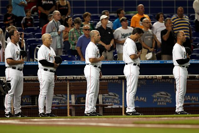 MIAMI, FL - APRIL 16: Manager Mike Redmond (L) of the Miami Marlins observes a moment of silence for the Boston Marathon victims before a game against the Washington Nationals at Marlins Park on April 16, 2013 in Miami, Florida. (Photo by Marc Serota/Getty Images)
