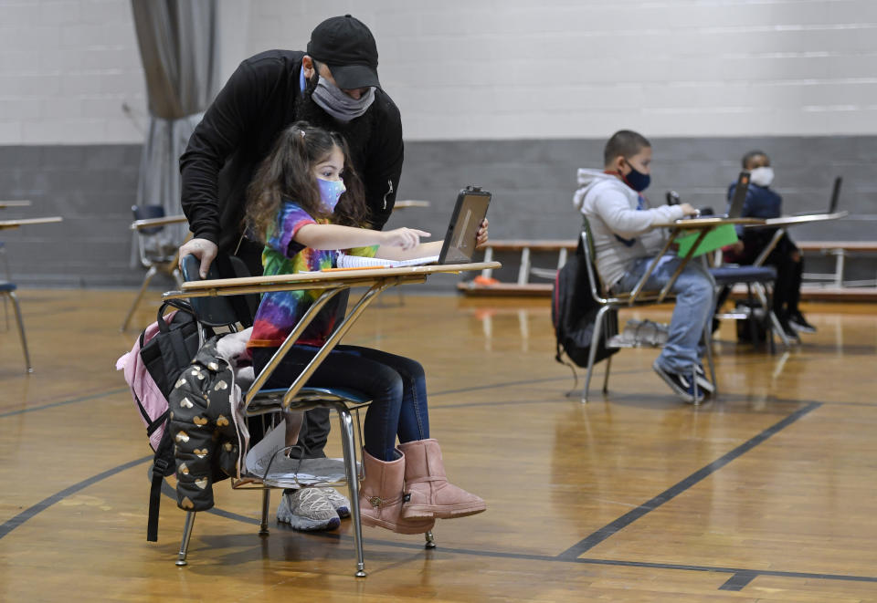 Jordan Rodriguez helps Christina Pagan, 7, with her school work at a Boys' and Girls' Club location in Pennsylvania. (Ben Hasty/MediaNews Group/Reading Eagle via Getty Images)