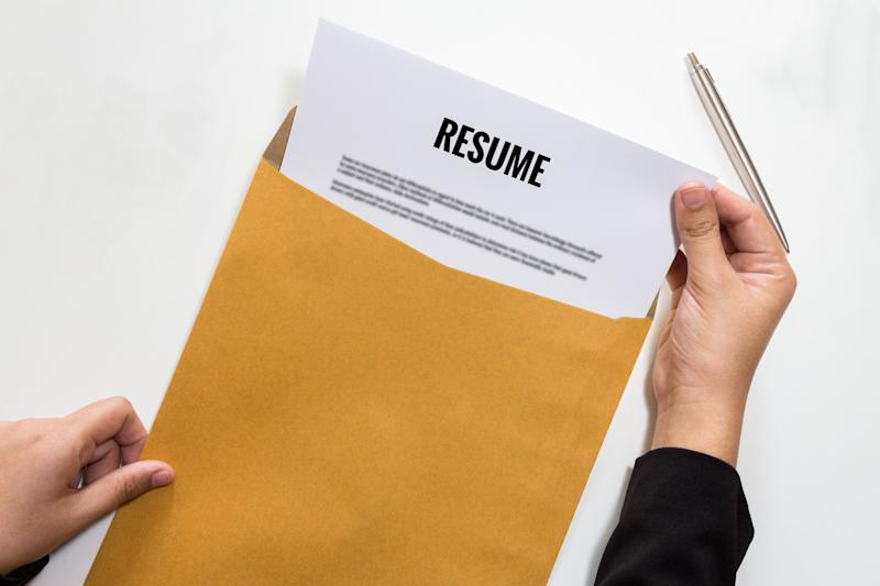 Hands remove a resume from a yellow folder. Image: Getty