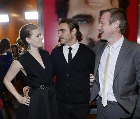 """Cast members Adams and Phoenix stand next to writer/director Spike Jonze at the film premiere of """"Her"""" at the Directors Guild of America in Hollywood"""