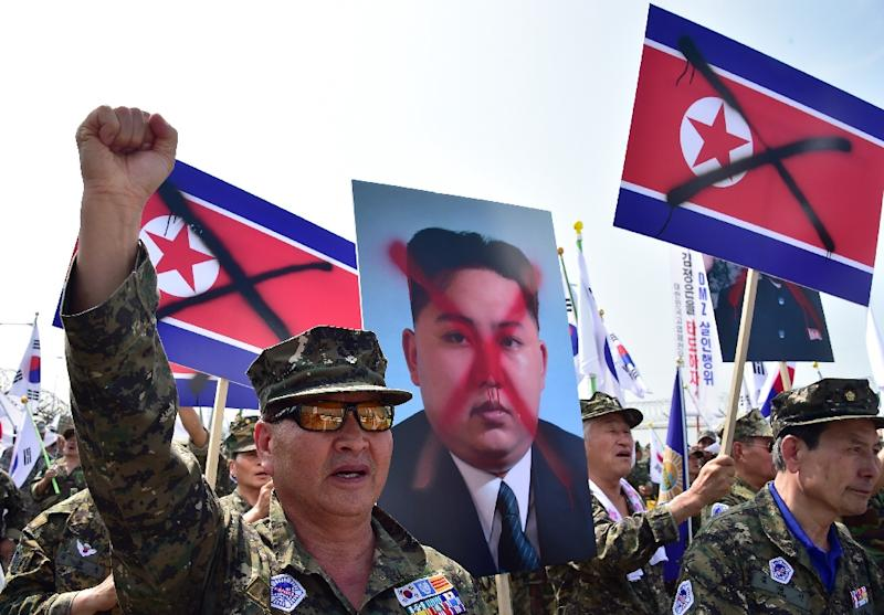 South Korean veterans hold placards showing spray-painted portraits of North Korean leader Kim Jong-Un, during an anti-North Korea protest in Paju, on August 13, 2015 (AFP Photo/Jung Yeon-Je)