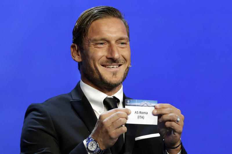 Former Italian player Francesco Totti shows the name ofAS Roma, who will play in Group C during the UEFA Champions League draw at the Grimaldi Forum, in Monaco, Thursday, Aug. 24, 2017. (AP Photo/Claude Paris)