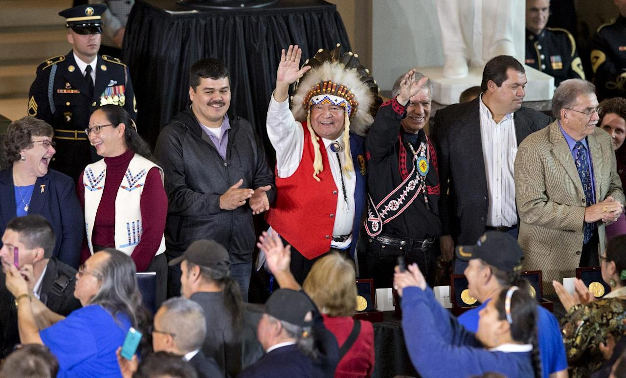 Representatives of Native American tribes celebrate during a Congressional Gold Medal ceremony honoring Indian code talkers who used their unique languages as a means of secret communication that enemy troops could not decipher, especially during World War II, at the Capitol in Washington, Wednesday, Nov. 20, 2013. Wallace Coffey, chief of the Comanche Nation in Oklahoma, raises his hand at center. (AP Photo/J. Scott Applewhite)