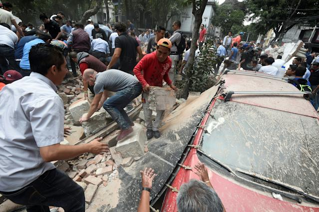 <p>People remove debris of a building which collapsed after a quake rattled Mexico City on September 19, 2017.<br> A powerful earthquake shook Mexico City on Tuesday, causing panic among the megalopolis' 20 million inhabitants on the 32nd anniversary of a devastating 1985 quake. The US Geological Survey put the quake's magnitude at 7.1 while Mexico's Seismological Institute said it measured 6.8 on its scale. The institute said the quake's epicenter was seven kilometers west of Chiautla de Tapia, in the neighboring state of Puebla.<br> (Photo: Alfredo Estrella/AFP/Getty Images) </p>