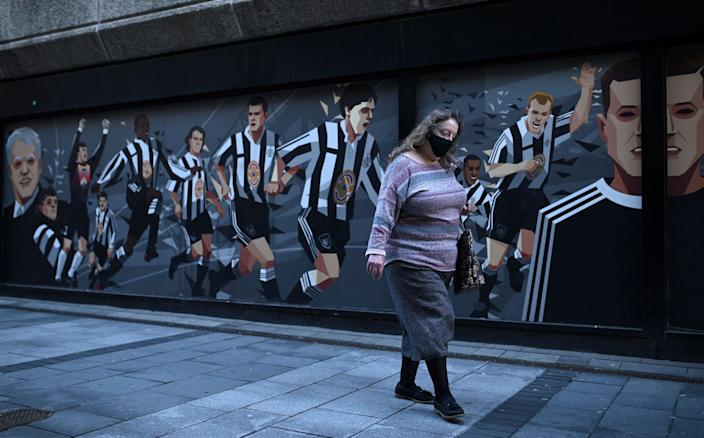 Woman wearing a face mask in Newcastle, where tighter regulations are coming in on 30 September (AFP via Getty Images)