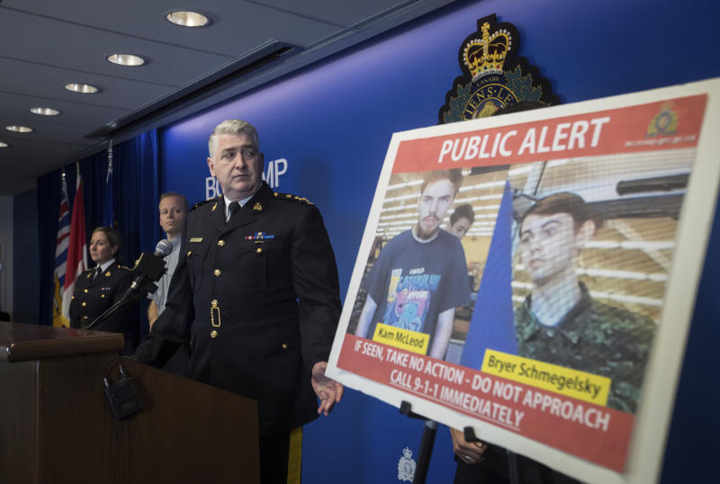 Security camera images recorded in Saskatchewan of Kam McLeod, 19, and Bryer Schmegelsky, 18, are displayed as Royal Canadian Mounted Police Assistant Commissioner Kevin Hackett steps away from the podium after speaking during a news conference in Surrey, British Columbia, on Tuesday, July 23, 2019. RCMP say two British Columbia teenagers who were first thought to be missing are now considered suspects in the deaths of three people in northern British Columbia. The bodies of Australian Lucas Fowler, his girlfriend Chynna Deese, of Charlotte, N.C., and an unidentified man were found a few kilometers from the teens' burned-out vehicle. (Darryl Dyck/The Canadian Press via AP)