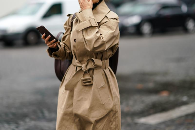 A guest wears a beige trench coat, outside Chanel, during Paris Fashion Week in October 2019 [Photo: Getty]