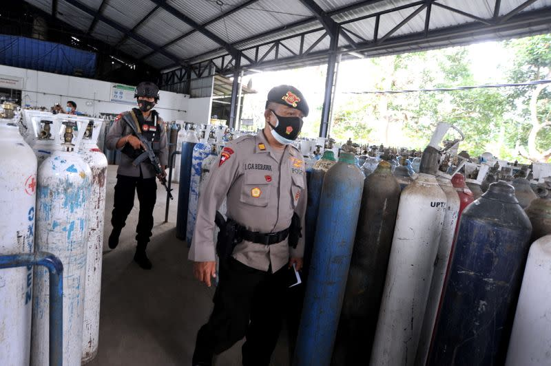 Police officers walk as they guard the oxygen distribution at a refill factory amid the coronavirus disease (COVID-19) outbreak in Mengwi, Badung, Bali