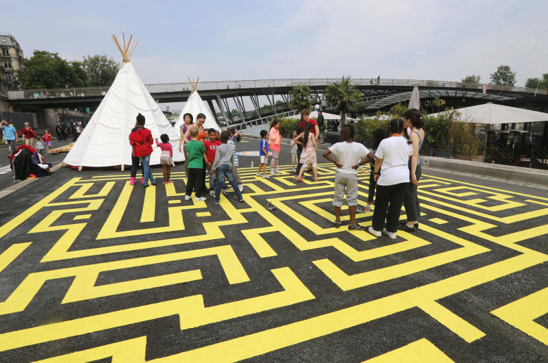 Children play on the renovated Left Bank of the Seine river where a new promenade has been inaugurated, Wednesday, June 19, 2013 in Paris. The 2.3 km (1.4 miles) walkway offers gardens, cafes, culture and sports activities. (AP Photo/Jacques Brinon)