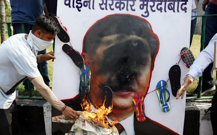 Protesters deface a poster of Chinese president Xi Jinping in India - RAMINDER PAL SINGH/EPA-EFE/Shutterstock