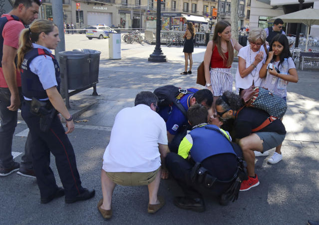 <p>A person is treated in Barcelona, Spain, Thursday, Aug. 17, 2017 after a white van jumped the sidewalk in the historic Las Ramblas district, crashing into a summer crowd of residents and tourists and injuring several people, police said. (AP Photo/Oriol Duran) </p>
