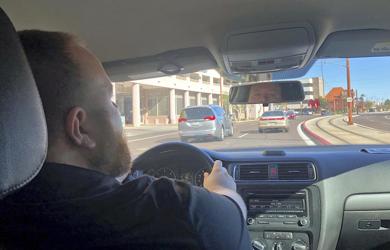 Uber driver David Kueneman, 34, talks Thursday, Dec. 19, 2019, about a new increase being imposed by Phoenix starting Feb. 1, 2020 on ride-hailing companies offering curbside service at Phoenix Sky Harbor International Airport. (AP Photo/Anita Snow)