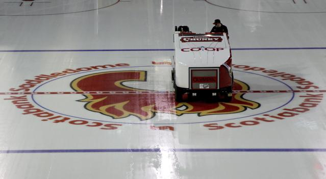 A Zamboni crosses over the Calgary Flames logo as preparations proceed for the start of a shortened NHL season at the Saddledome in Calgary, Alberta, on Monday Jan. 7, 2013. (AP Photo/The Canadian Press, Jeff McIntosh)