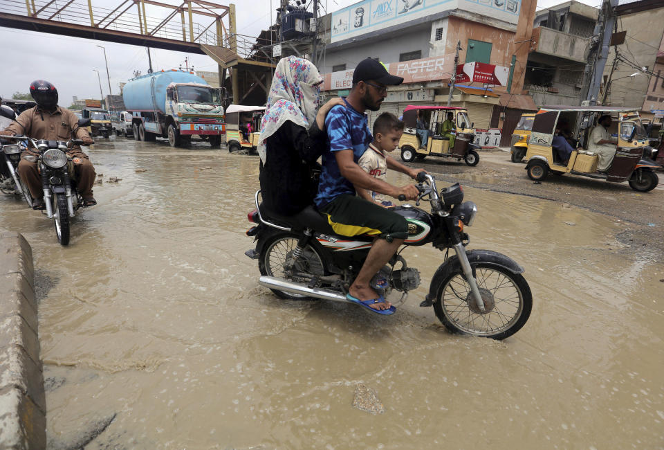 Motorcyclists drive through a road flooded by heavy rainfall in Karachi, Pakistan, Sunday, Aug. 9, 2020. Three days of heavy monsoon rains triggering flash floods killed at least dozens people in various parts of Pakistan, as troops with boats rushed to a flood-affected district in the country's southern Sindh province Sunday to evacuate people to safer places. (AP Photo/Fareed Khan)