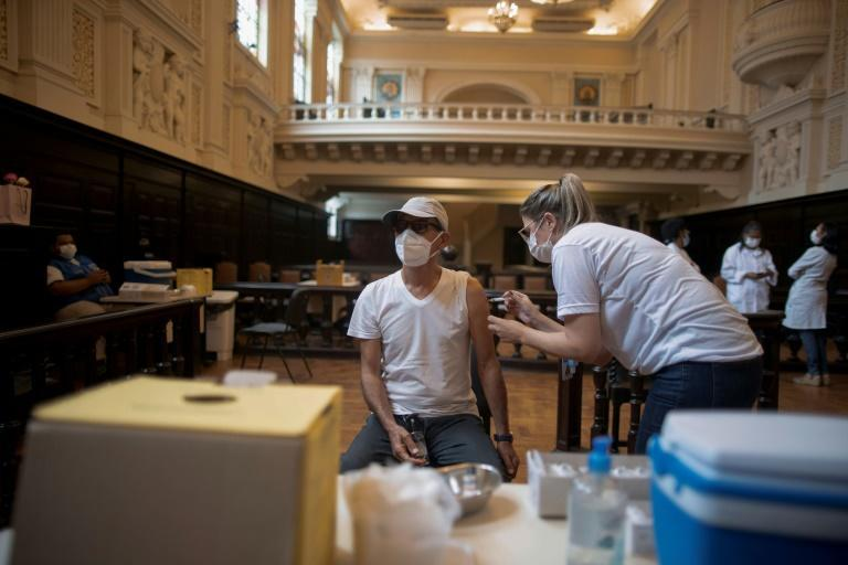 A man is inoculated against the coronavirus with a CoronaVac vaccine at the Justice Palace in Rio de Janeiro on March 31, 2021