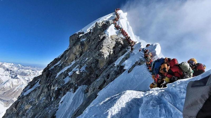 A queue of climbers line the top of Mount Everest.