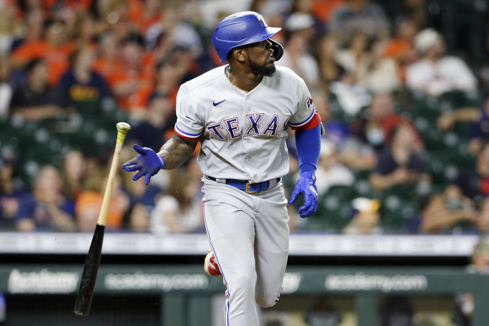Texas Rangers' Adolis Garcia flips his bat as he watches his home run against the Houston Astros during the eighth inning of a baseball game Friday, May 14, 2021, in Houston. (AP Photo/Michael Wyke)