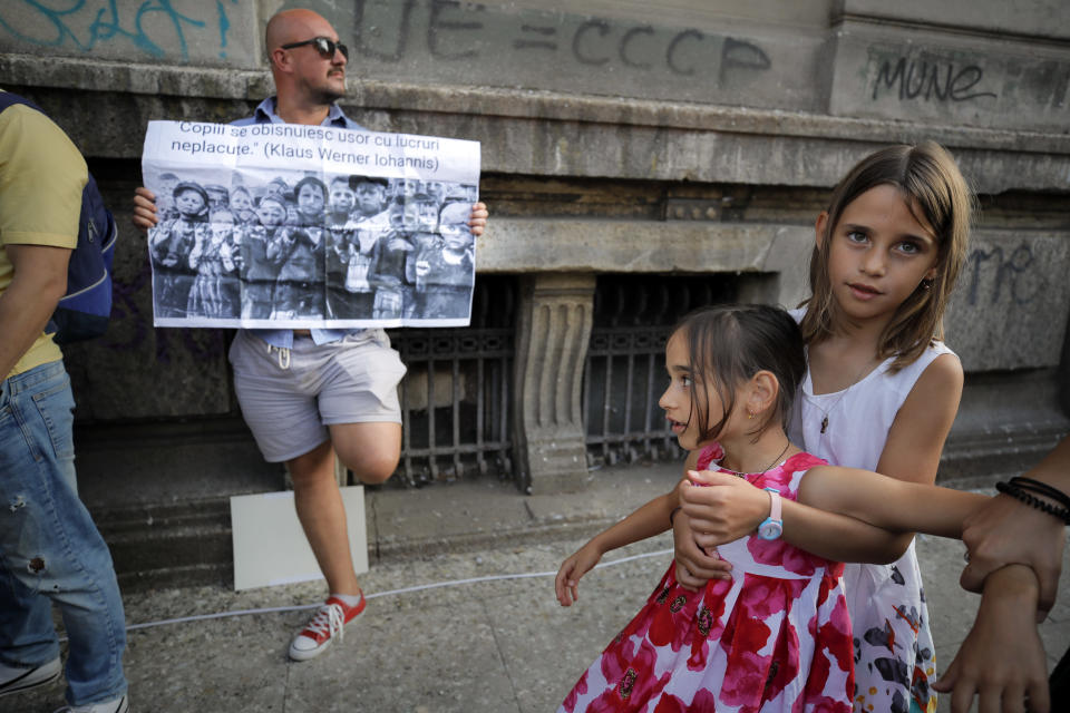 """In this photo taken on Saturday, Sept. 19, 2020 kids play next to a man holding a banner showing children in a concentration camp and a paraphrase from a statement by Romanian President Klaus Iohannis that reads """"Children get used to unpleasant things easily"""" during a protest against the COVID-19 pandemic restrictions in Bucharest, Romania. Across the Balkans and the rest of the nations in the southeastern corner of Europe, a vaccination campaign against the coronavirus is overshadowed by heated political debates or conspiracy theories that threaten to thwart the process. In countries like the Czech Republic, Serbia, Bosnia, Romania and Bulgaria, skeptics have ranged from former presidents to top athletes and doctors. Nations that once routinely went through mass inoculations under Communist leaders are deeply split over whether to take the vaccines at all. (AP Photo/Vadim Ghirda)"""