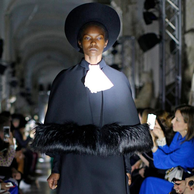 A model wears a creation inspired by clerical attire.