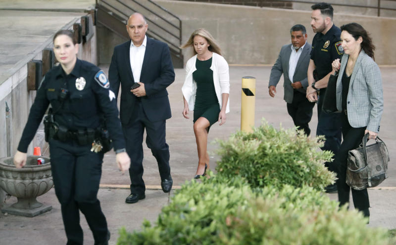 In this Tuesday, Sept. 24, 2019 photo, Amber Guyger, center, walks flanked by security while arriving for her murder trial at the Frank Crowley Courthouse in downtown Dallas. Security has been ramped up around the white former Dallas police officer's high-profile trial for murder in the killing of her unarmed black neighbor. The Dallas Police Association says threats have forced the group to hire private security for Guyger and her lawyers.  (AP Photo/LM Otero)