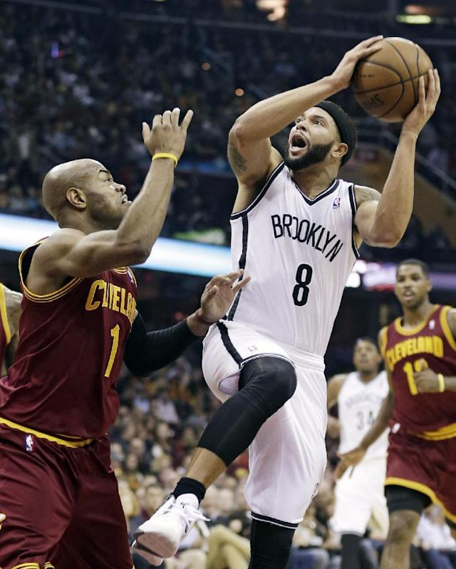 Brooklyn Nets' Deron Williams (8) tries to shoot over Cleveland Cavaliers' Jarrett Jack (1) during the first quarter of an NBA basketball game Wednesday, Oct. 30, 2013, in Cleveland. (AP Photo/Tony Dejak)