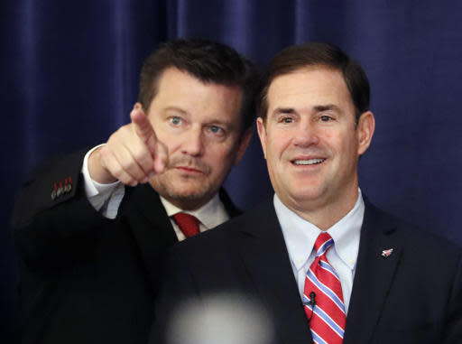 CORRECTS SPELLING TO BIDWILL, NOT BIDWELL AS ORIGINALLY SENT - Arizona Cardinals owner Michael Bidwill, left, gestures beside Arizona Gov. Doug Ducey as they wait for NFL commissioner Roger Goodall to announce Phoenix has been awarded the 2023 Super Bowl during the NFL owner's spring meeting Wednesday, May 23, 2018, in Atlanta. (AP Photo/John Bazemore)
