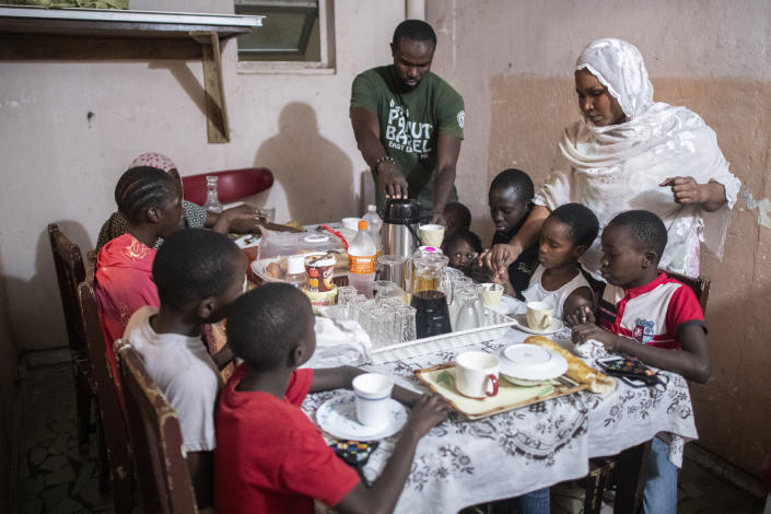 Bara Tambedou, center, and his wife Mame Sey, right, break the fast with their family on the first day of the Muslim holy month of Ramadan, in Dakar, Senegal, Saturday, April 25, 2020. (AP Photo/Sylvain Cherkaoui)