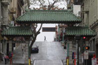 FILE - In this April 4, 2020, file photo, a pedestrian crosses Grant Street behind the Dragon Gate, an entrance to Chinatown in San Francisco. San Francisco reached the least-restrictive yellow tier for a brief period in October, the only urban area to do so, before an alarming surge in cases forced a retreat. Los Angeles never emerged from the most restrictive tier until March 2021. (AP Photo/Jeff Chiu, File)