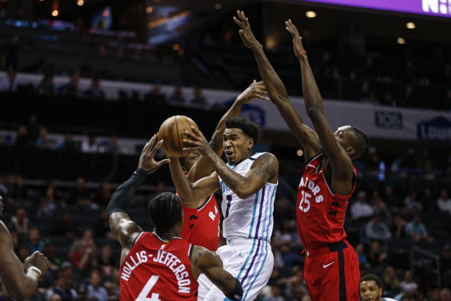 Charlotte Hornets guard Malik Monk, center, drives to the basket past Toronto Raptors forwards Rondae Hollis-Jefferson (4) and Chris Boucher (25) during the first half of an NBA basketball game in Charlotte, N.C., Wednesday, Jan. 8, 2020. (AP Photo/Nell Redmond)