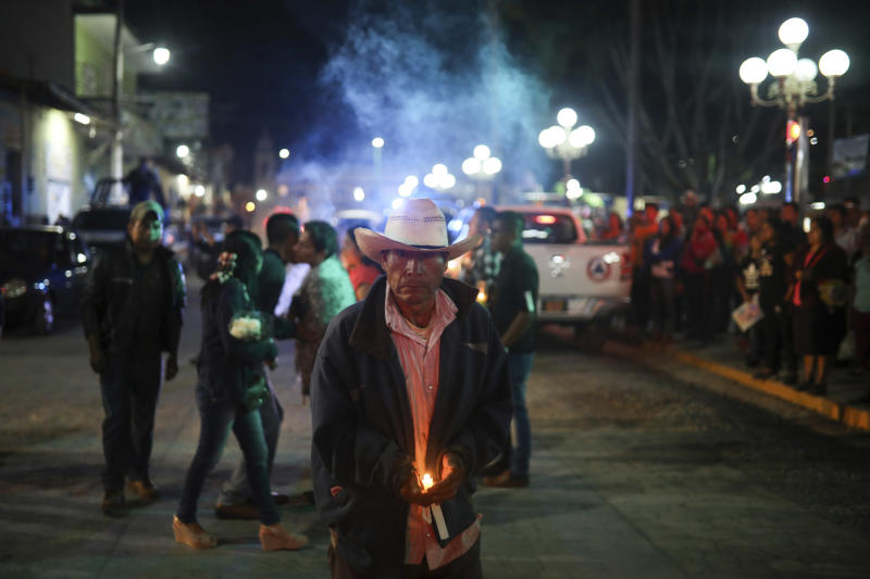 A man carries a candle as mourners gather to greet the hearse bringing the body of Maricela Vallejo, the slain 27-year-old mayor of Mixtla de Altamirano, to her aunt's house for her wake, in Zongolica, Veracruz state, Mexico, Thursday, April 25, 2019. Vallejo, her husband, and a driver were assassinated Thursday by multiple gunmen as they drove along a highway. (AP Photo/Felix Marquez)