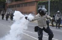 A Bolivarian National Police throw a teargas bomb toward demonstrators during a protest in Caracas, Venezuela, Saturday, April 8, 2017. Opponents of President Nicolas Maduro protest on the streets of Caracas on Saturday as part of a week-long protest movement that shows little sign of losing steam. (AP Photo/Fernando LLano)