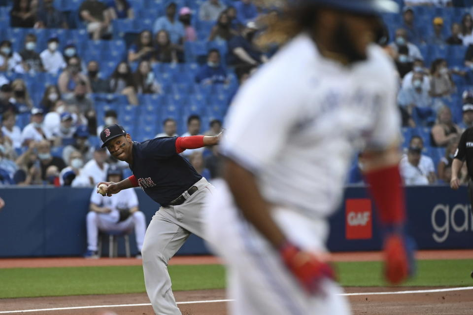 Boston Red Sox third baseman Rafael Devers, left, throws to first base but not in time to put out Toronto Blue Jays' Vladimir Guerrero Jr., right, in the first inning of the second game of a baseball doubleheader in Toronto, Saturday Aug. 7, 2021. (Jon Blacker/The Canadian Press via AP)