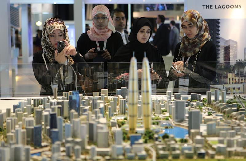 FILE - In this Wednesday, Oct. 9, 2013 file photo, Visitors take photos and notes of The Lagoons project, a development which will be situated in the Mohammed Bin Rashid City, during the second day of a real estate fair called Cityscape Global in Dubai, United Arab Emirates. A global property consultant said Monday there are worrying signs that Dubai could be facing another economic bubble after property prices jumped more than 22 percent last year and rents by 17 percent. (AP Photo/Kamran Jebreili, File)