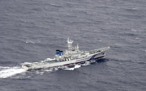 A Japan Coast Guard patrol vessel sails on the water at the area where two US Marine Corps aircraft are thought to have crashed - Credit: REUTERS