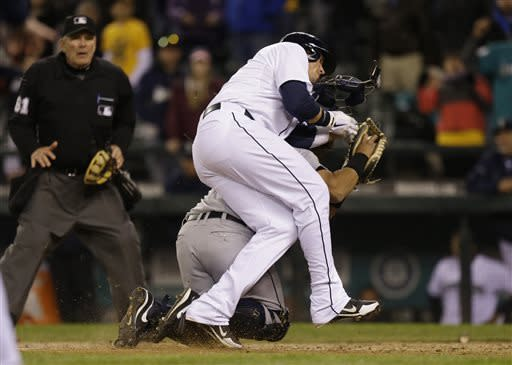 Seattle Mariners' Justin Smoak collides with Detroit Tigers catcher Brayan Pena and is out at the plate while trying to score in the 14th inning of a baseball game, Wednesday, April 17, 2013, in Seattle. The Tigers beat the Mariners 2-1 in 14 innings. (AP Photo/Ted S. Warren)