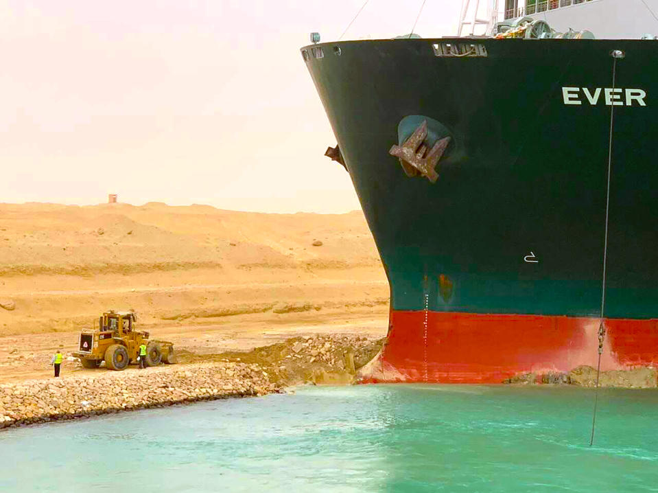 A cargo ship, named the Ever Given, sits with its bow stuck into the wall Wednesday, March 24, 2021, after it become wedged across Egypt's Suez Canal and blocked all traffic in the vital waterway. An Egyptian official warned Wednesday it could take at least two days to clear the ship. (Suez Canal Authority via AP)