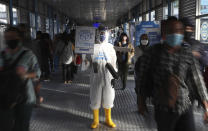 An employee wearing protective gear as a precaution against the new coronavirus holds banner displaying information about the virus and those infected at the Harmoni Central Busway station in Jakarta Thursday, July 16, 2020. Indonesia has the highest numbers of coronavirus infections and fatalities in Southeast Asia. (AP Photo/Achmad Ibrahim)