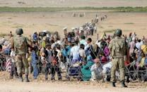 Turkish soldiers stand guard as Syrian Kurds wait behind the border fence to cross into Turkey near the southeastern town of Suruc in Sanliurfa province, September 19, 2014. REUTERS/Stringer