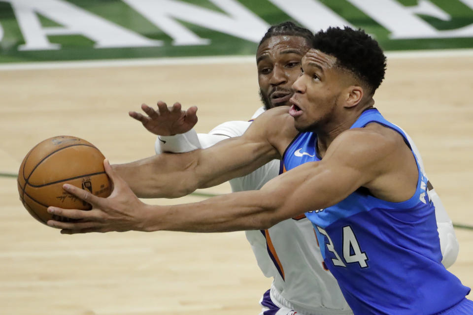 Milwaukee Bucks' Giannis Antetokounmpo, right, is fouled by Phoenix Suns' Jae Crowder, left, during the first half of an NBA basketball game Monday, April 19, 2021, in Milwaukee. (AP Photo/Aaron Gash)