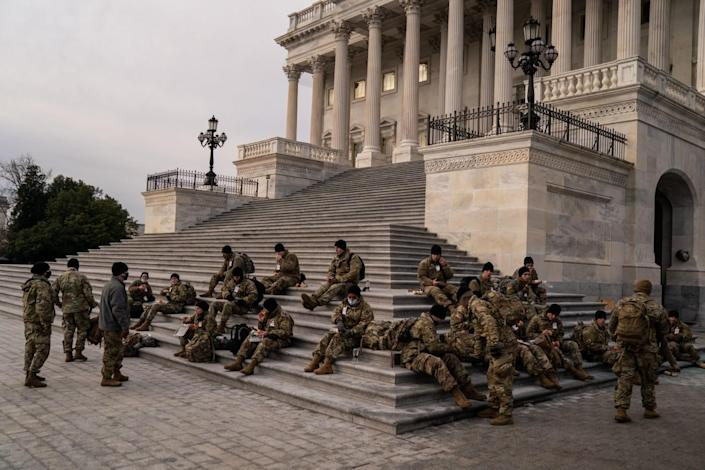 National Guard members sit on the steps to the U.S. Capitol as they eat breakfast.