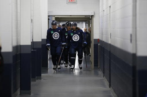 Winnipeg Jets players head off the ice during the first day of the NHL training camp in Winnipeg, Manitoba, Friday, Sept. 13, 2019. (John Woods/The Canadian Press via AP)