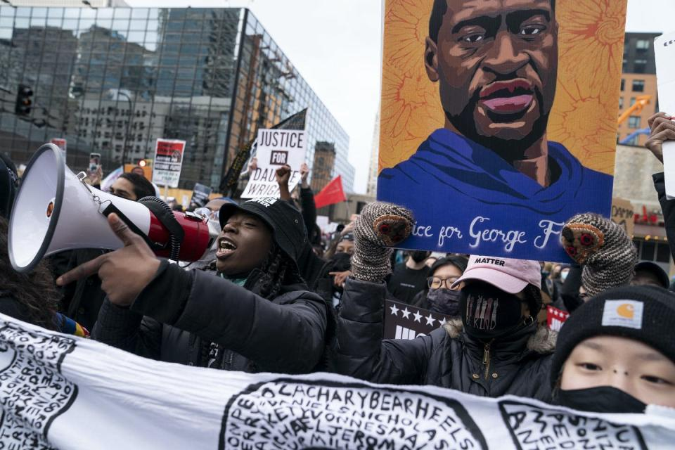 Demonstrators march carrying bullhorns and a placard of George Floyd