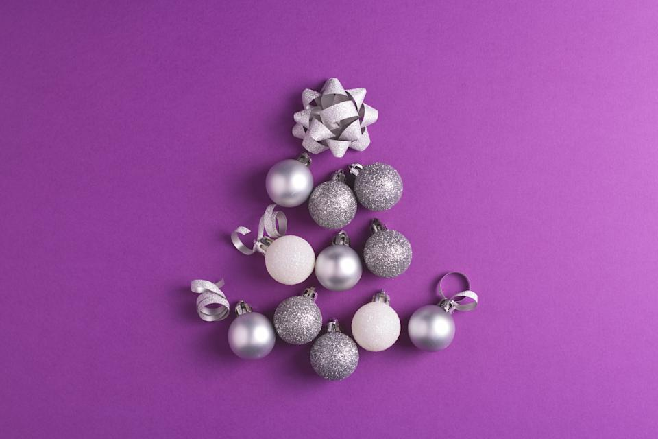 Christmas tree made of metallic baubles on purple background. Top view. Christmas and New Year concept.