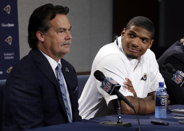 St. Louis Rams seventh-round draft pick Michael Sam, right, listens as coach Jeff Fisher speaks during a news conference at the NFL football team's practice facility Tuesday, May 13, 2014, in St. Louis. (AP Photo/Jeff Roberson)