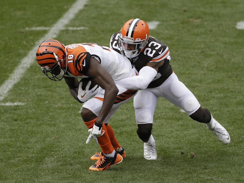 In this photo taken on Sunday, Sept. 29, 2013, Cleveland Browns cornerback Joe Haden, right, tackles Cincinnati Bengals A.J. Green during an NFL football game in Cleveland. With impressive performances the past two weeks, Cleveland's defense is establishing itself as one of the NFL's most dominant units. On Sunday, the Browns held the Bengals to just two field goals in a 17-6 win and Haden contained star wide receiver Green. (AP Photo/Tony Dejak)