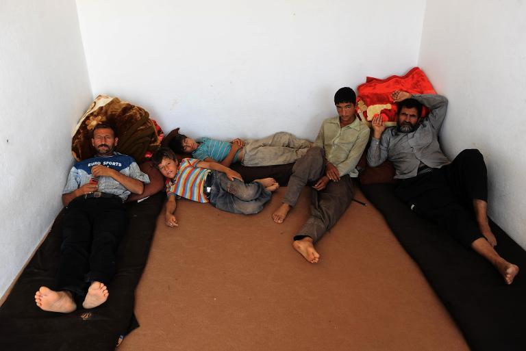 Afghan refugees are pictured on September 22, 2013 at an UNHCR centre in Herat after being deported from Iran