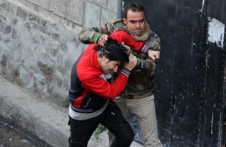An Indian police official scuffles with a Kashimiri youth after the firefight in Srinagar